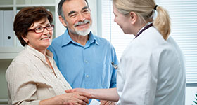 Doctor shaking hands with older couple