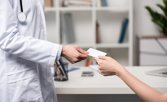 image of a doctor handing a card to a female patient