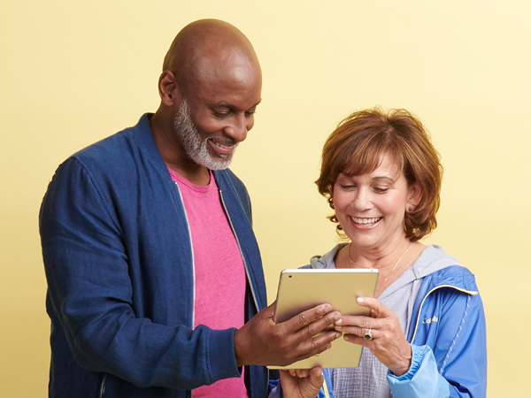 older man and woman looking at a tablet