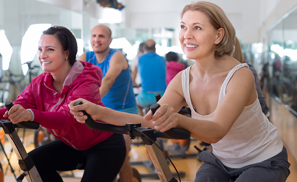 a small group of people riding an exercise bike intensely while smiling