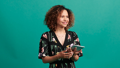 woman with curly hair holding a tablet