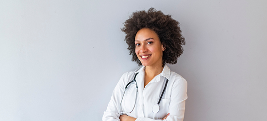 female doctor in white coat against grey background