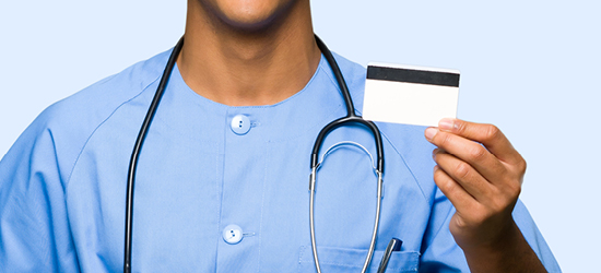 man in blue scrubs holding prescription card