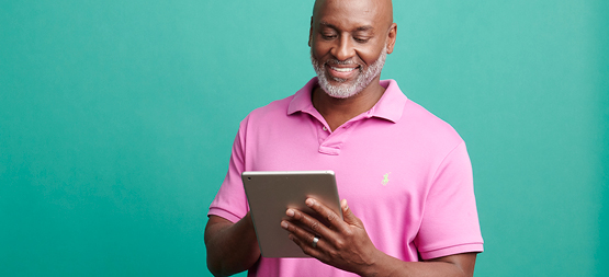 man in pink shirt using a tablet
