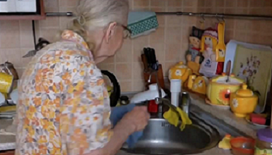 old woman washing dishes in kitchen sink