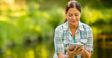 woman on tablet outdoors