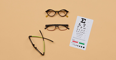 pairs of glasses with eye chart