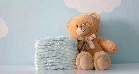 teddy bear and diapers on sky background