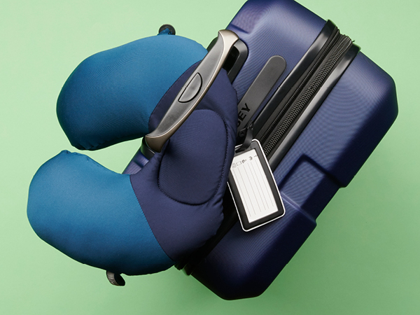 Travel pillow looped through suitcase handle