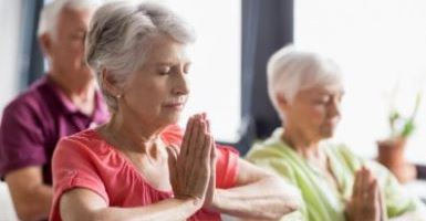 Elderly group of individuals in yoga class with folded hands