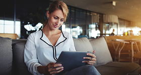 woman wearing business clothes looking at tablet
